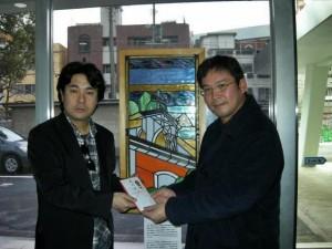 長崎カトリックセンター、牢屋の窄殉教記念教会のステンドグラスの前でカトリック長崎大司教区下窄神父様に寄付金を贈呈。